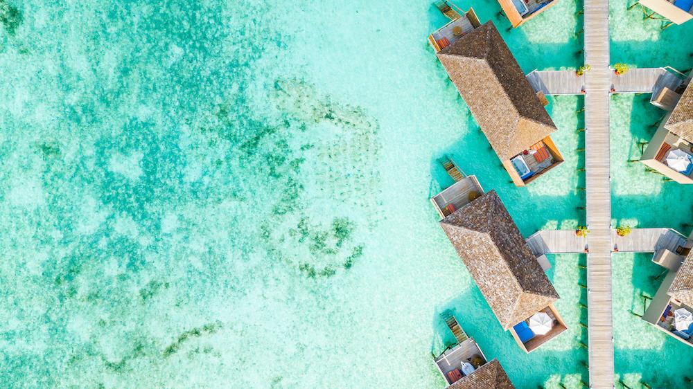 Aerial top view water villa at Maldives island, Beautiful tropical Maldives resort hotel.