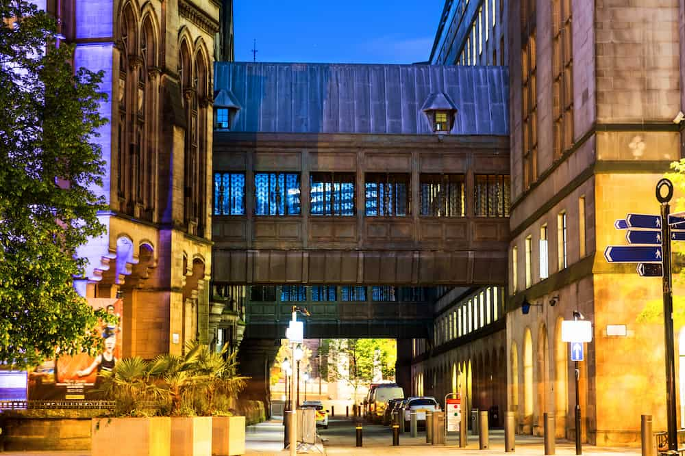 Manchester, England. Illuminated old historical buildings in the city center of Manchester, UK at night
