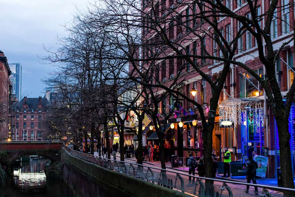 MANCHESTER UNITED KINGDOM -Evening view of a lit up street and canal in the city of Manchester in the north of England.