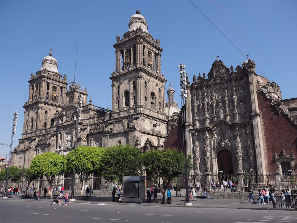 MEXICO CITY, NORTH AMERICA on : Scenic Metropolitan Cathedral building of the Assumption of Mary at Mexico City in Zocalo square with clear blue sky in warm sunny winter day.