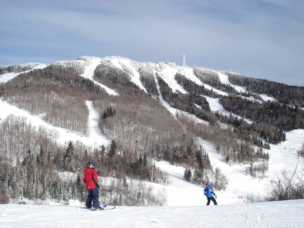 a nice view of mont-tremblant ski resort in quebec eastern canada with 2 skiers