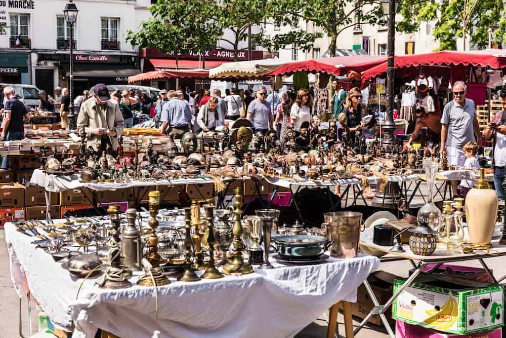 Paris France - People choosing rare and used books wooden masks and figures of African culture at the historic flea Aligre Market (Marche d'Aligre) in the Bastille district.