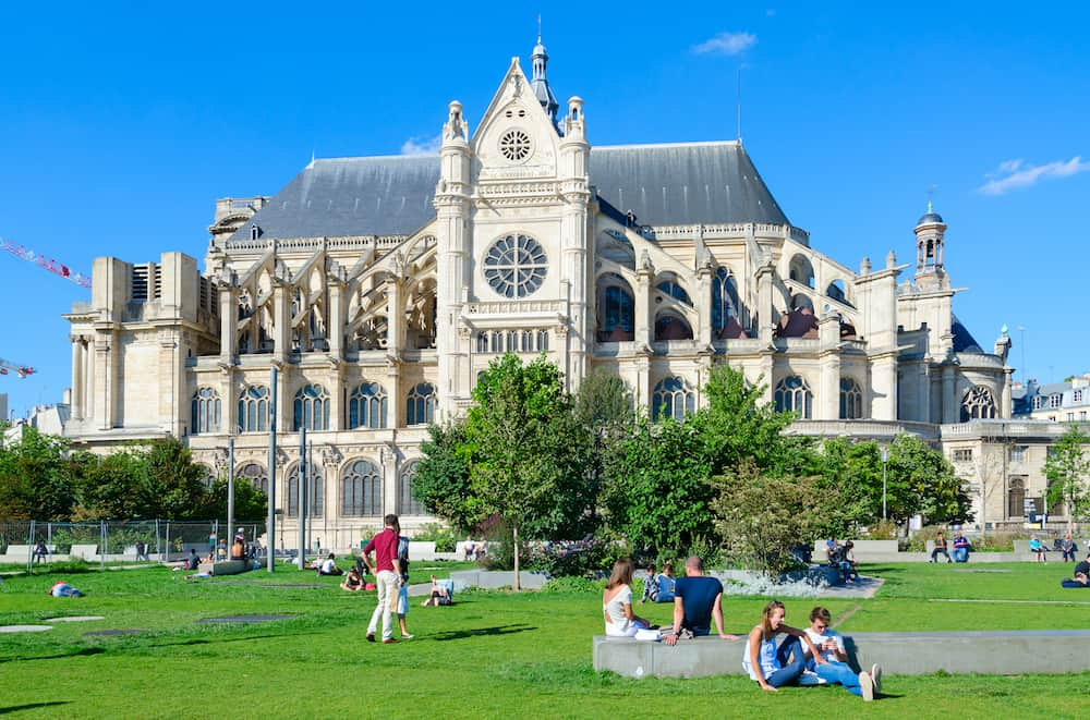 PARIS, FRANCE - Unknown people rest on green lawn near Catholic Church of St. Eustache, or Saint-Eustache (glise Saint-Eustache), Paris, France