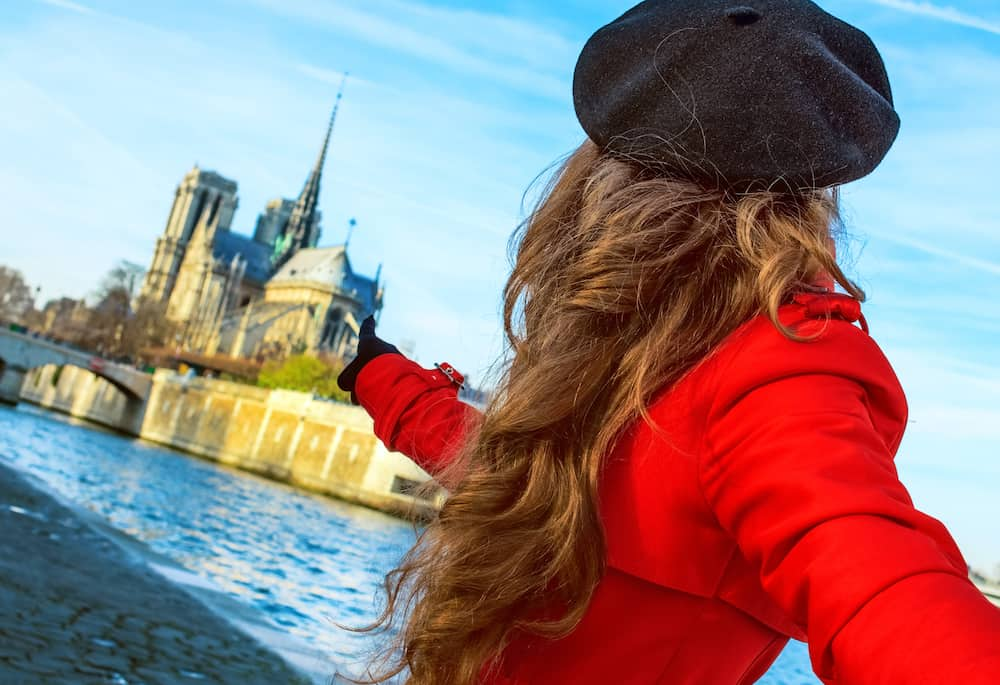 Bright in Paris. modern woman in red trench coat on embankment near Notre Dame de Paris in Paris, France holding friends hand and pointing at Notre Dame de Paris