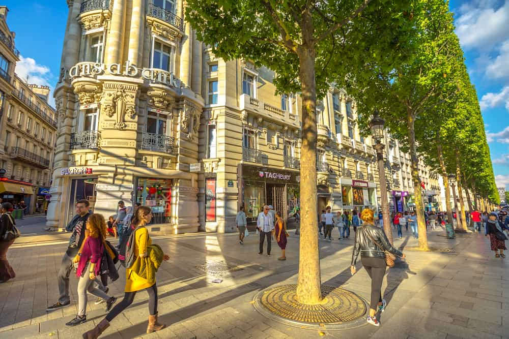 Paris, France - people walk on the most famous avenue in Paris Champs Elysees, known for luxury and shopping that starts from Place de La Concorde to Place Charles de Gaulle. Sunny day.