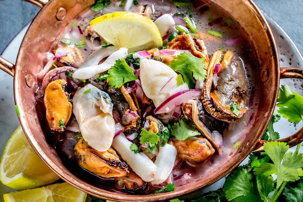 Peruvian Latin American seafood shellfish ceviche cebiche. Raw seafoods - mussels shrimps clams squides marinated in lemon juice with red onion and coriander in cooper bowl gray slate background.
