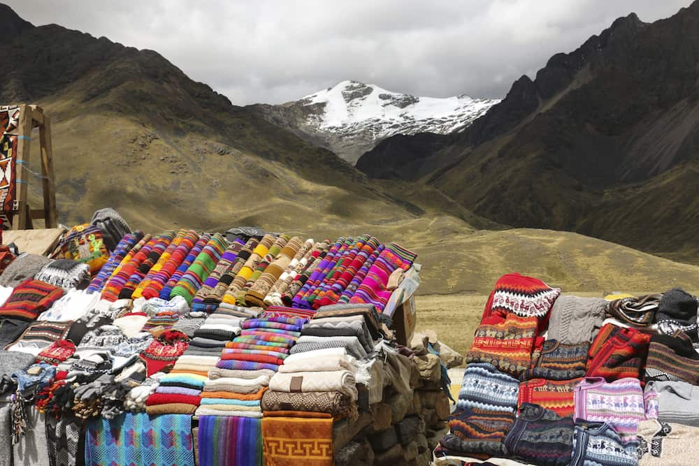 Scarves hats in traditional style of different colors on the market. The road Cusco-Puno Peru