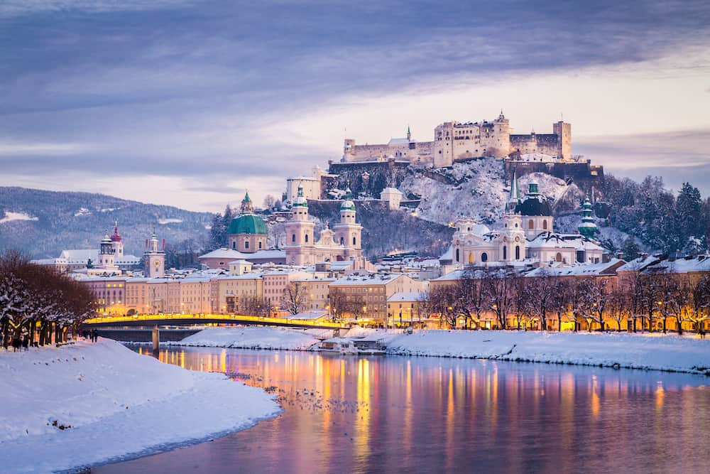 Classic view of the historic city of Salzburg with famous Festung Hohensalzburg and Salzach river illuminated in beautiful twilight during scenic Christmas time in winter Salzburger Land Austria