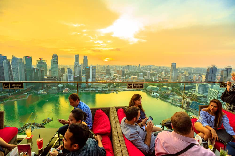 Singapore -: lifestyle people enjoy sunset and panoramic views from rooftop SkyBar CE THE VI on 57th floor of Marina Bay Sands hotel and casino. Financial district skyline on background.