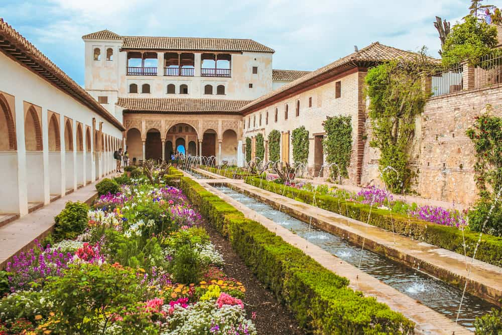 Beautiful garden with many flowers of different colors and a corridor fountain in Granada, Generalife, Spain