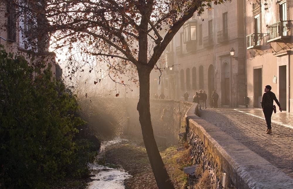 GRANADA, ANDALUCIA, SPAIN -Carrera del Darro along the river in afternoon sunhaze in Granada, Andalucia, Spain