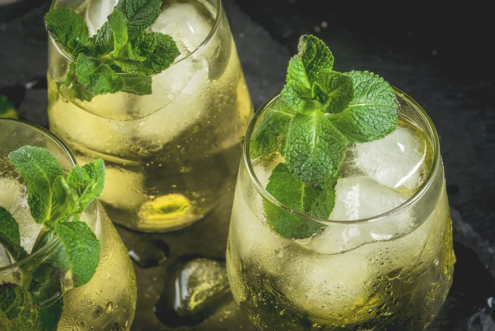 Traditional Spanish alcoholic drink Rebujito cocktail - white wine carbonated water (soda) mint lemon juice. On a black slate board close view