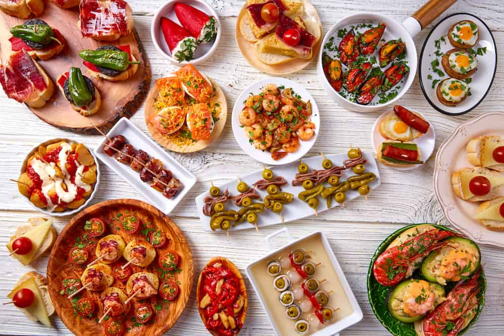 Tapas mix and pinchos food from Spain recipes also pintxos on a white wood board