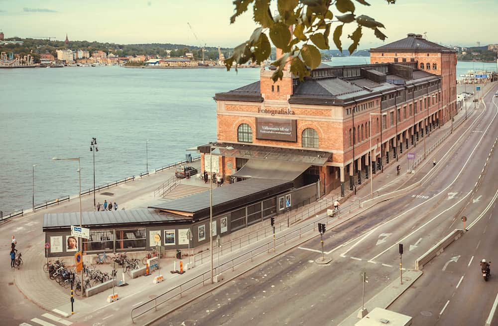 STOCKHOLM, SWEDEN - Brick bilding of the cultural center Fotografiska and street traffic of swedish capital. Sweden with 10,5 million peope ranks high in life expectancy