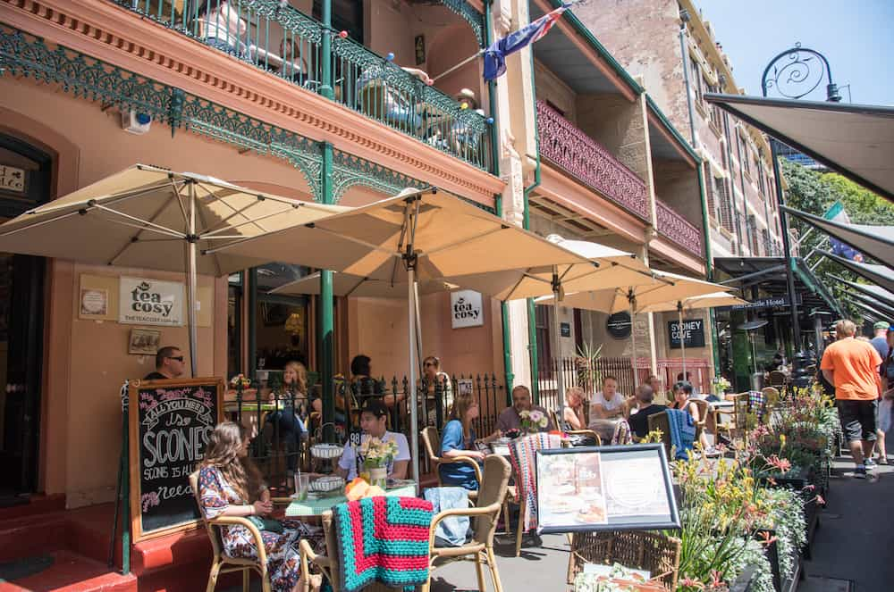 SYDNEY,NSW,AUSTRALIA-: The Tea Cosy sidewalk cafe with people and handmade blankets in The Rocks district of Sydney, Australia.