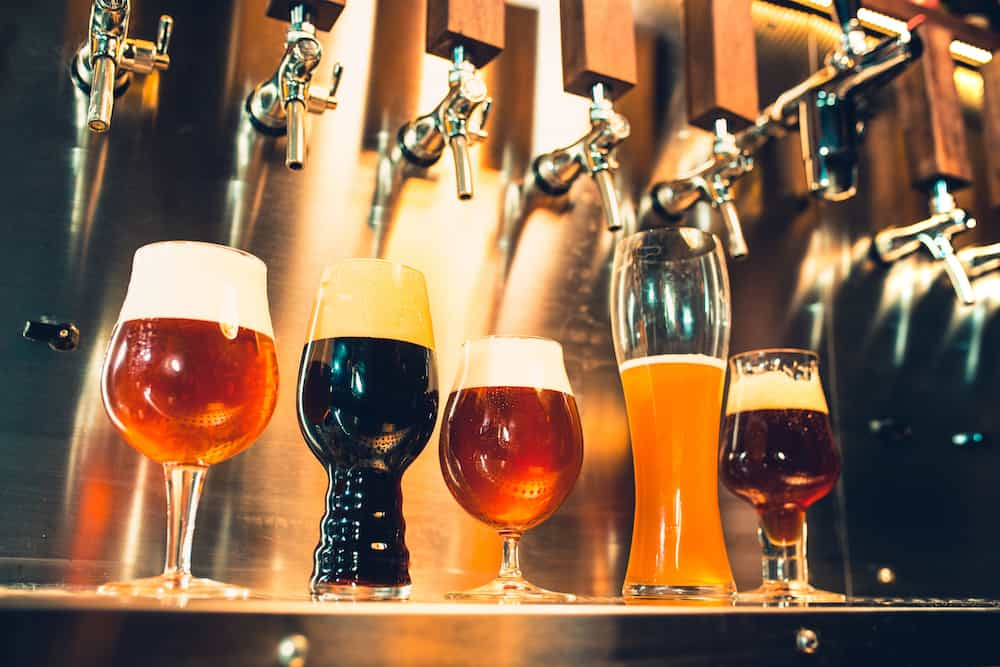 The beer taps in a pub. nobody. Selective focus. Alcohol concept. Vintage style. Beer craft. Bar table. Steel taps. Shiny taps. Glass of beer