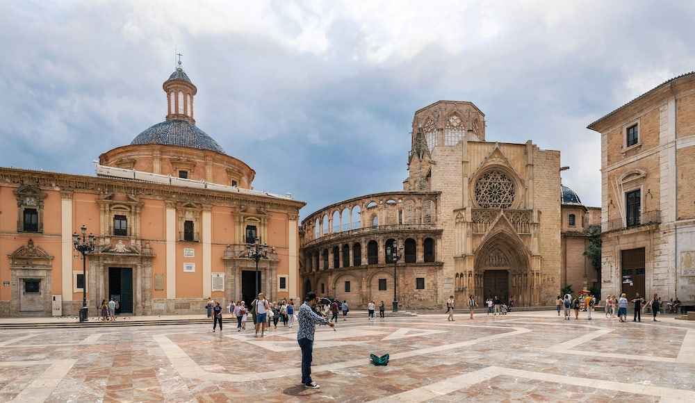 Valencia, Spain - Street artist plays violin among tourists on Plaza de la Virgen Cathedral Square. Located in a central of Valencia.