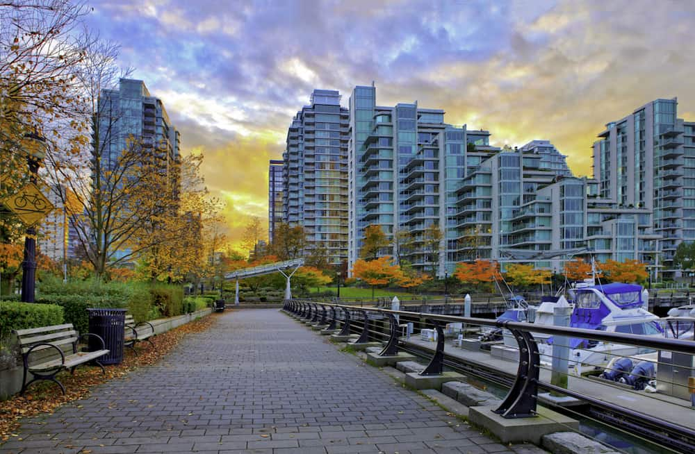 Paved pathway along Coal Harbour and modern residential buildings in the background. Vancouver Canada.