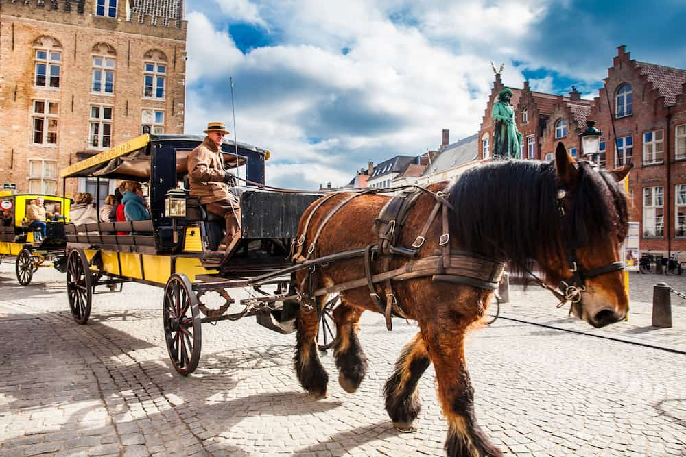 BRUGES, BELGIUM - : People touring around the beautiful Bruges town on a carriage pulled by a horse