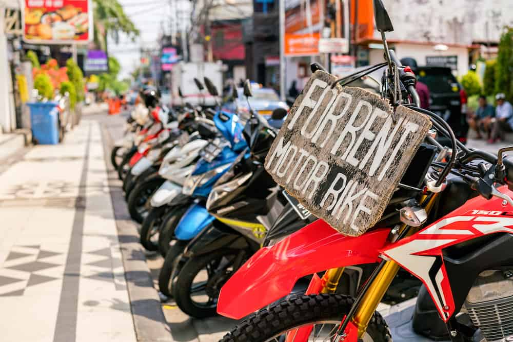 Motorcycles and scooters for rent on Legian Street in Kuta, Bali, Indonesia.