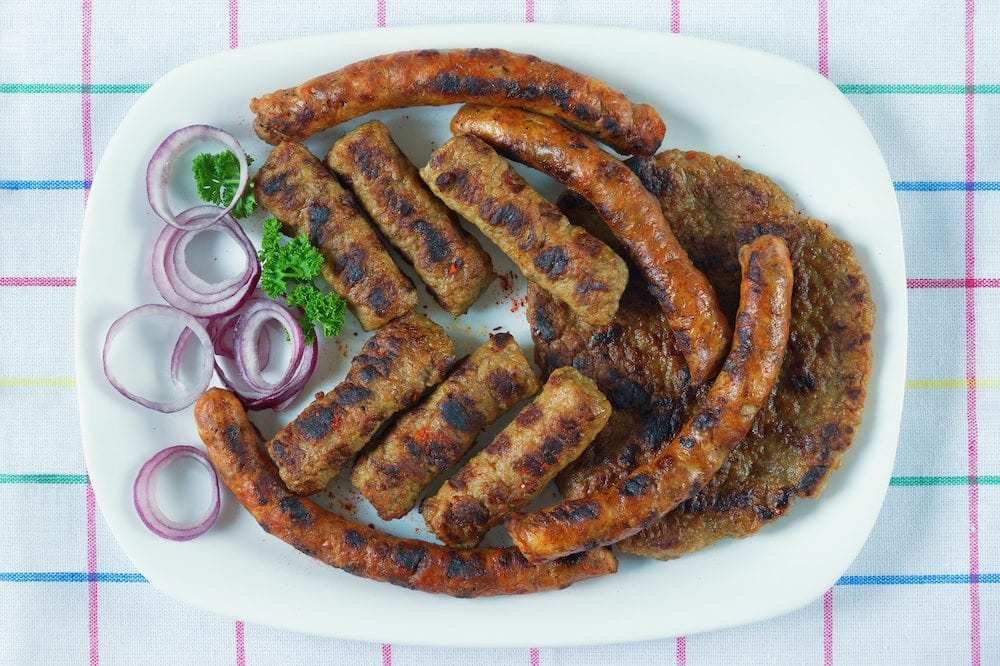 Balkan cuisine. Cevapi, kobasica and pljeskavica - grilled dish of minced meat. Flat lay