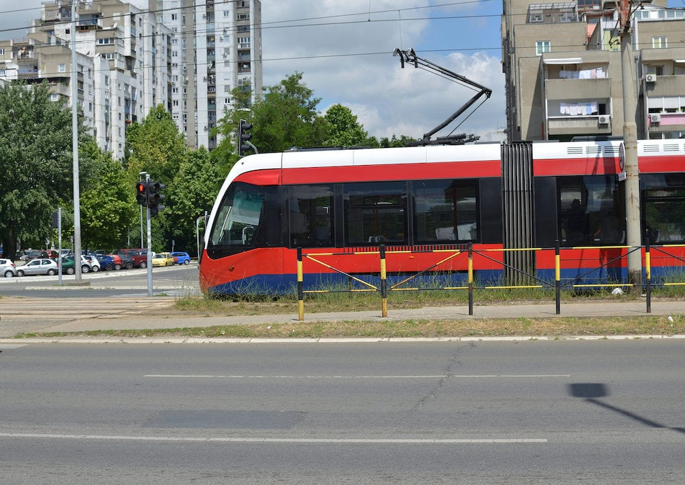 Red tram on a boulevard in a residential area of an European city - Belgrade Serbia