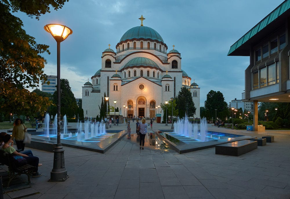 Belgrade, Serbia - Belgrade citizens and tourists have evening walk near Temple of Saint Sava. Fountains on the square near temple is illuminated by blue light.