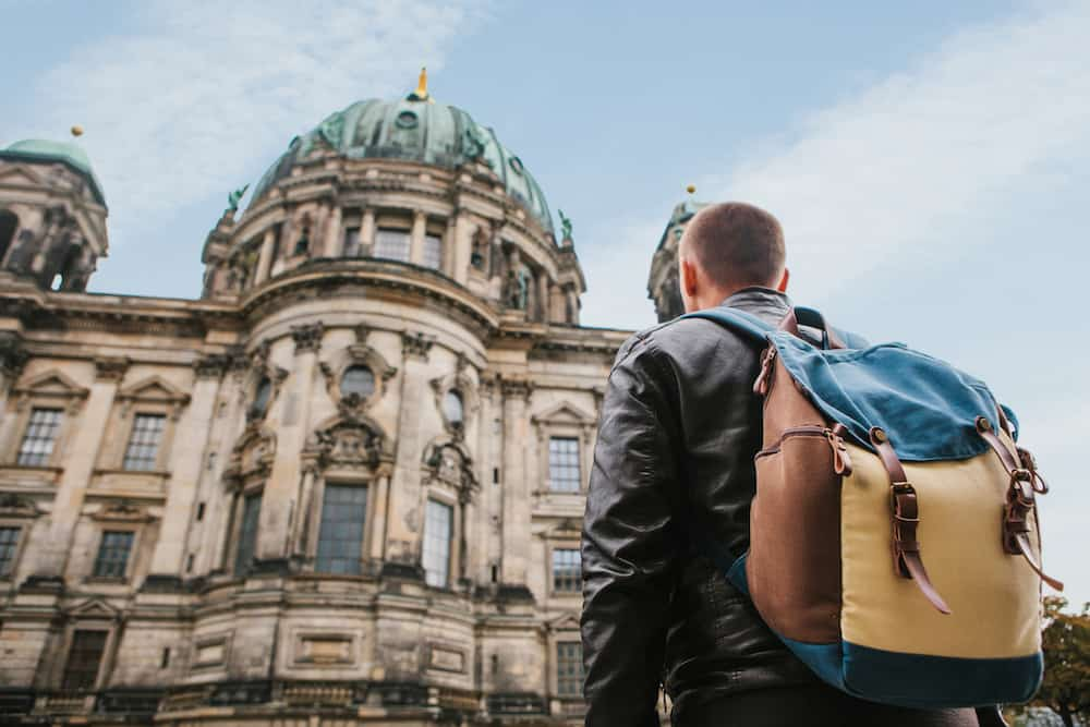 A tourist or traveler with a backpack looks at a tourist attraction in Berlin called Berliner Dom. Traveling in Germany.