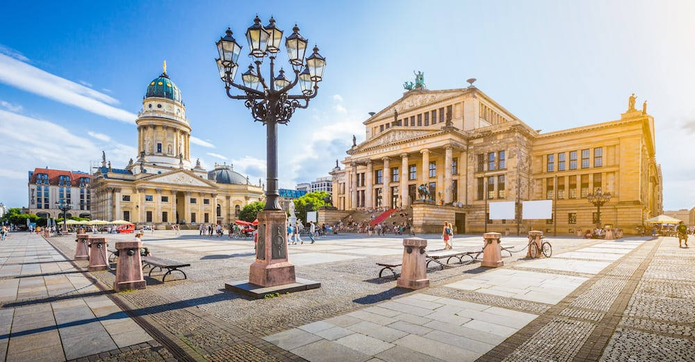 Panoramic view of famous Gendarmenmarkt square with Berlin Concert Hall and German Cathedral in golden evening light at sunset with blue sky and clouds in summer Berlin Mitte district Germany