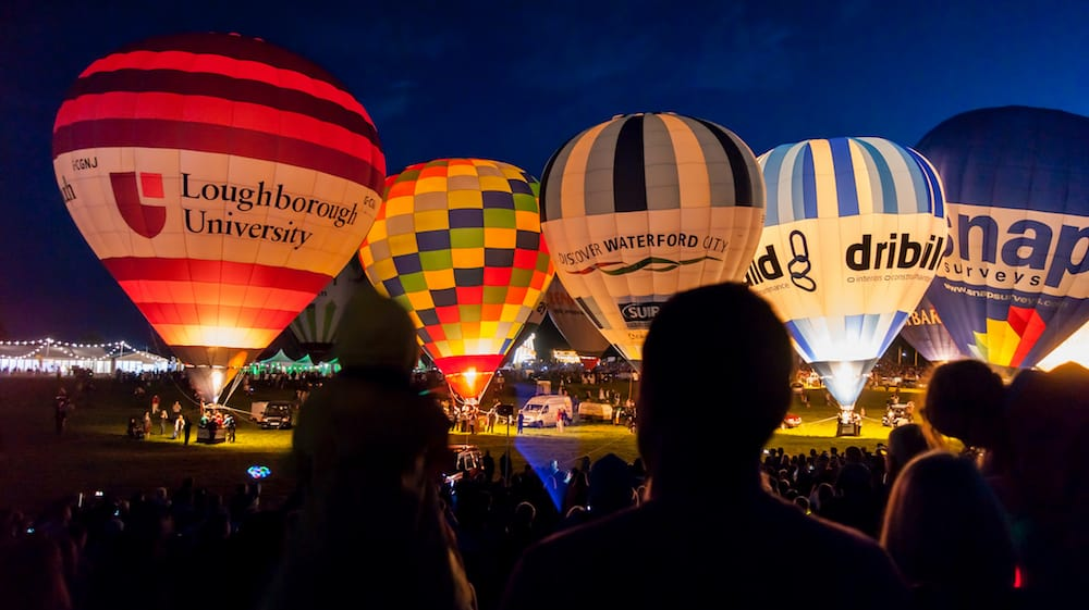 Bristol UK - A row of Hot Air Balloons glow at night for the Bristol Balloon Fiesta at Ashton Court