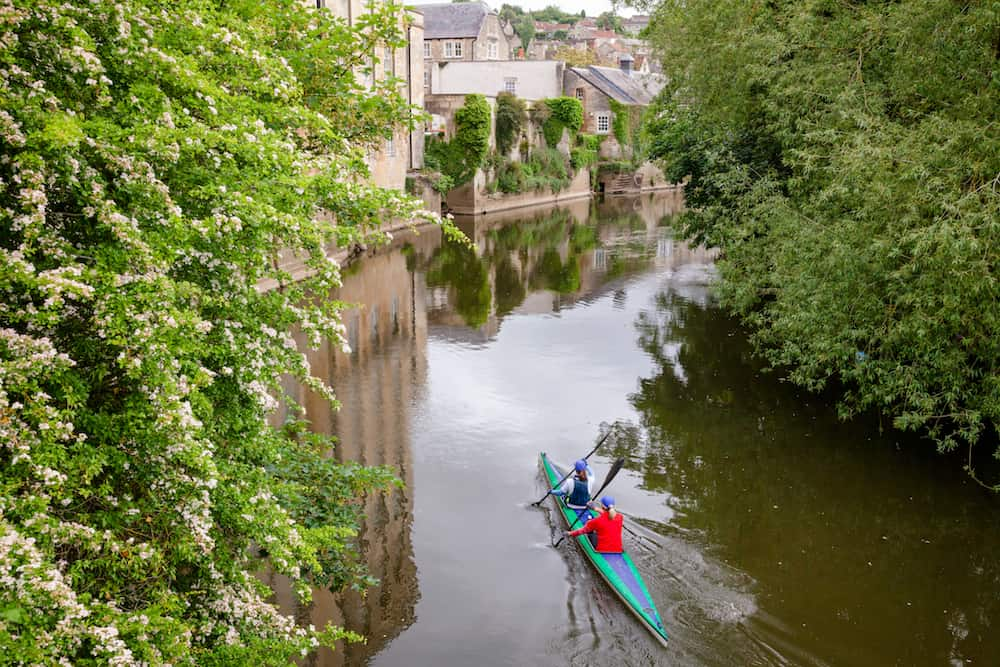 Two women kayaking down the River Avon (Bristol Avon) along scenic Bradford-on-Avon, a town and civil parish in West Wiltshire, Southwest England, UK