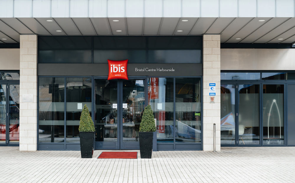 BRISTOL UNITED KINGDOM - ibis hotel entrance welcome door with red signage and designed trees and red carpet - clean hotel with luxury entrance - Ibis Bristol Centre Harbourside
