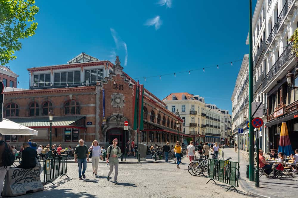 Brussels, Belgium - : People near the Halles Saint-Gery on a sunny day. In 1882, this was a covered market. Now it is well known for the many bars and restaurants in the area.