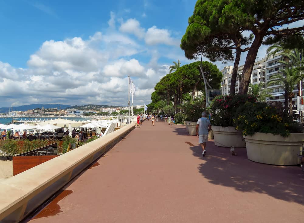 Cannes, France - Promenade de la Croisette in Cannes. France. Unidentified people are walking along the street.