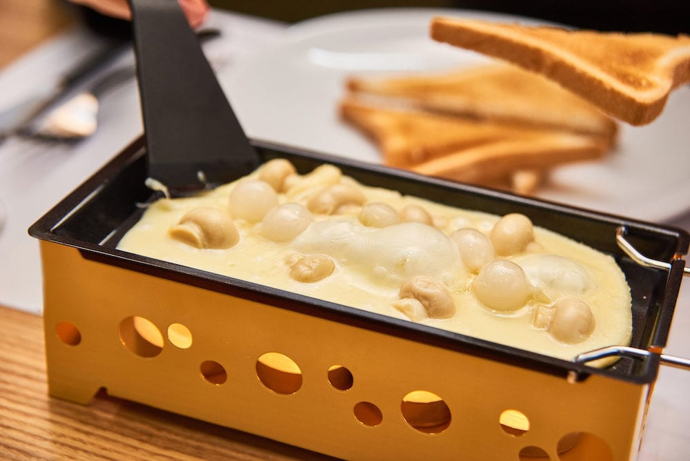 swiss food. cheese raclette with mushrooms on coupelles - special small skillet for a raclette