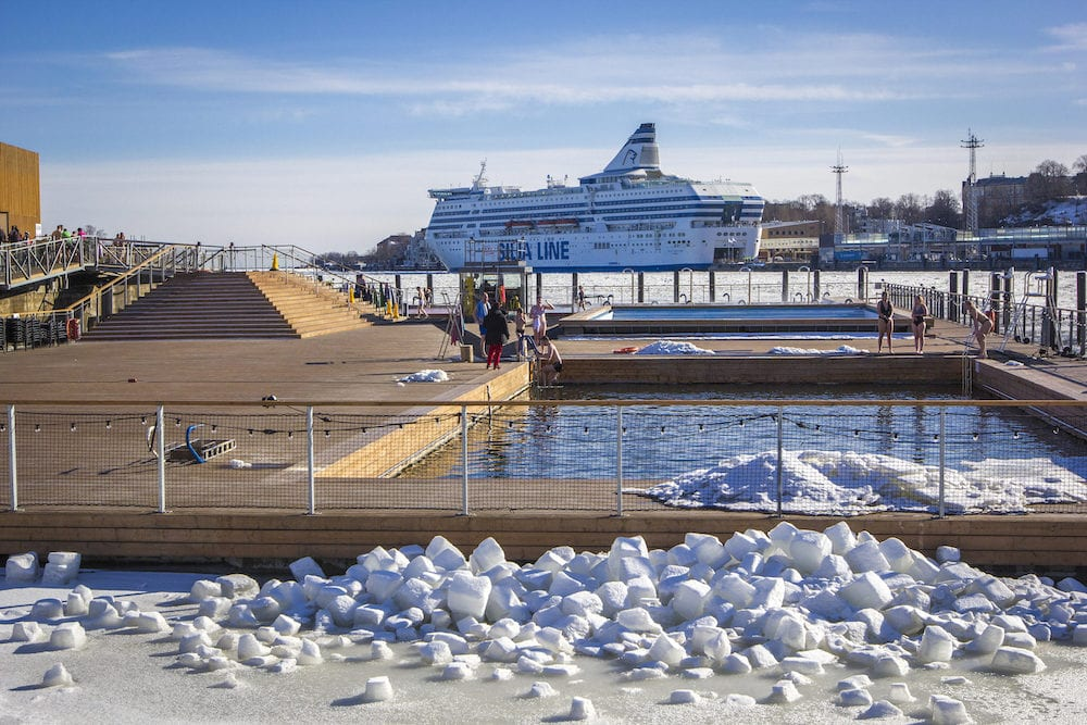 HELSINKI, FINLAND - : Allas Sea Pool- spa ; wellness hub with large pools with sea warm water and saunas for relax in South Harbour of Helsinki, in winter sunny day, passenger ferry in the background, Finland.