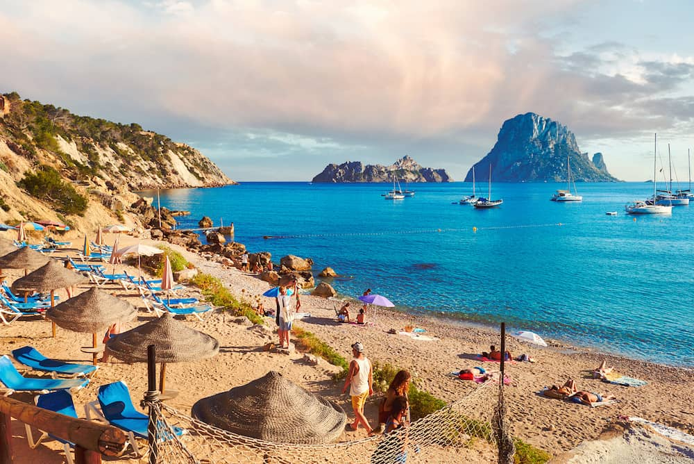Ibiza Island Spain - People enjoying the summer at Cala d'Hort beach. Cala d'Hort in summer is extremely popular beach have a fantastic view of the mysterious island of Es Vedra. Ibiza Island Balearic Islands. Spain