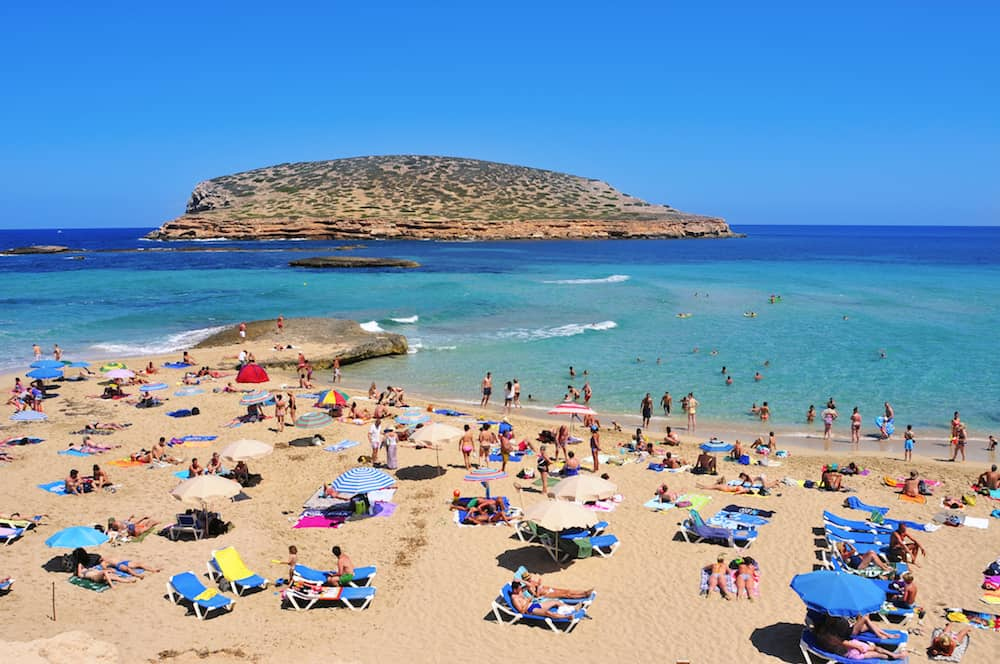 SAN ANTONIO, SPAIN - Sunbathers at Cala Conta beach in San Antonio, in Ibiza Island, Spain. Ibiza is a well-known summer tourist destination in Europe