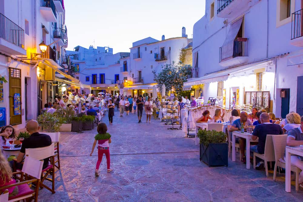 IBIZA, BOLOREAR ISLANDS, SPAIN - street in old town with strolling promenade tourists and vacationers visiting street cafes and restaurants in evening light of street lamps and sunset.