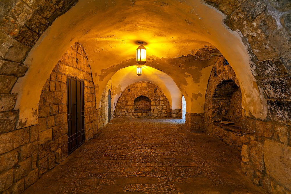 Ancient stone arched passage illuminated with lanterns in Old City of Jerusalem, Israel.