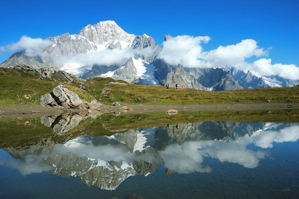 View of the south face of Mont Blanc mountain range reflected in a lake while two trekkers walking along the path. Val Veny Italy.