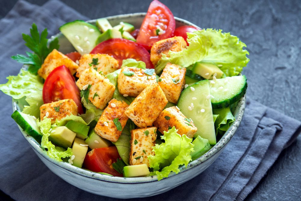 Fried Tofu Salad with Cucumbers Tomatoes Avocado and Sesame Seeds. Homemade asian vegetable and tofu salad in ceramic bowl on black stone background. Healthy asian diet vegan vegetarian salad food.