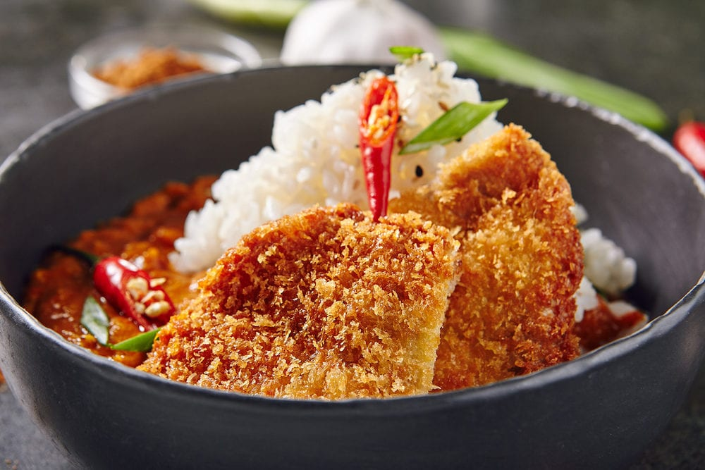 Hot Spicy Crispy Fried Pork Fillet with Curry and Rice on Dark Background. Katsu or Tonkatsu with Red Peppres, Meat Cutlet in Breadcrumbs, Tomatoes, Chilli Sauce, Greens and Herbs