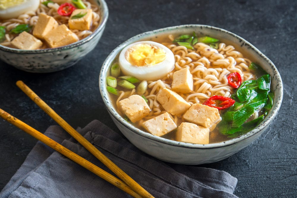 Japanese ramen soup with tofu and egg on dark stone background. Miso soup with ramen noodles and tofu in ceramic bowl asian traditional food.