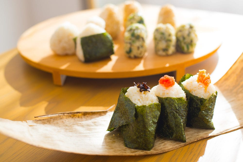 Showing how to make Rice Ball ''Onigiri'' is a typical meal in Japan. Japanese people grab some rice into balls with a shape of triangul in Tokyo, Japan.