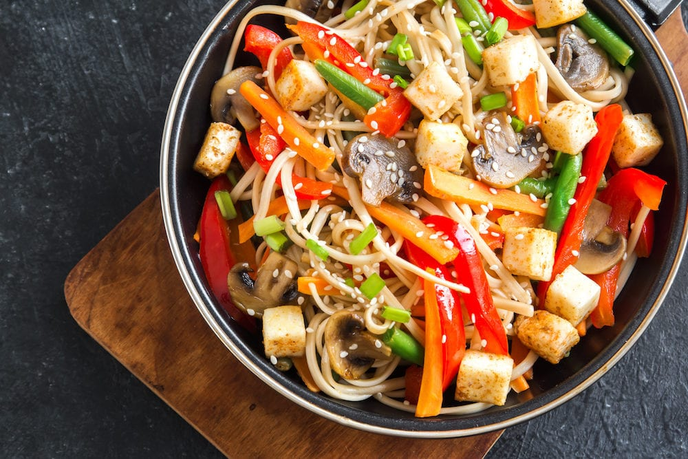 Stir fry with udon noodles, tofu, mushrooms and vegetables. Asian vegan vegetarian food, meal, stir fry in wok over black background, copy space.