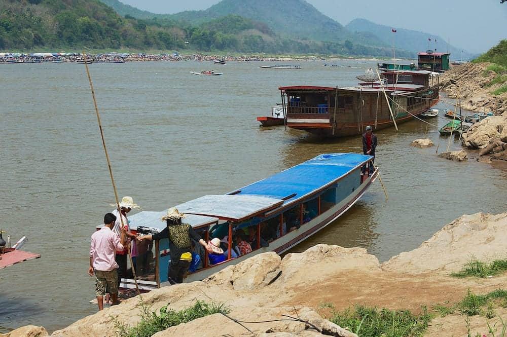 LUANG PRABANG, LAOS - Unidentified people embark to the traditional long boat to cross Mekong river in dry season in Luang Prabang, Laos.