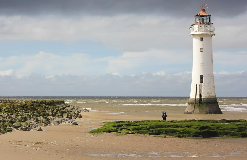 NEW BRIGHTON, ENGLAND, The Perch Rock Lighthouse in New Brighton, England. A couple watches the tide roll in at the Perch Rock Lighthouse in New Brighton Merseyside England