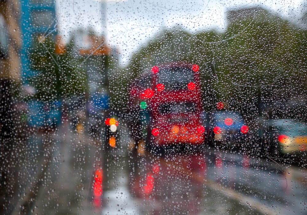 London traffic scene with Doubledecker bus seen through bus stop glass covered with rain drops - autumn rainy weather concept