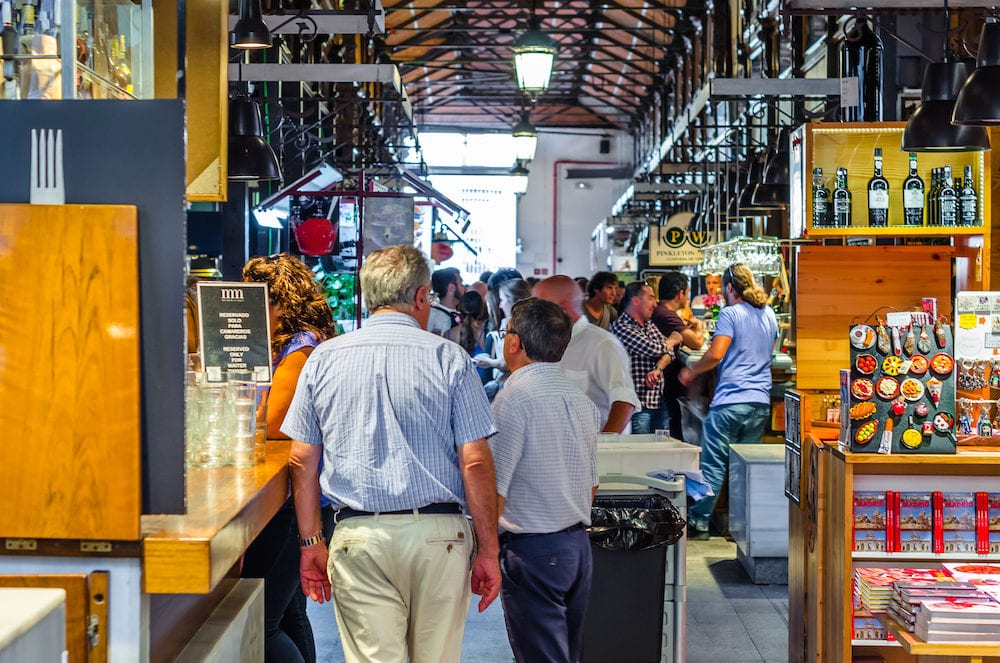 "MADRID, SPAIN - People visiting and enjoying drinks and tapas inside the historical ""Mercado de San Miguel"" (Market of San Miguel), popular among tourists, located in the center of Madrid, Spain"